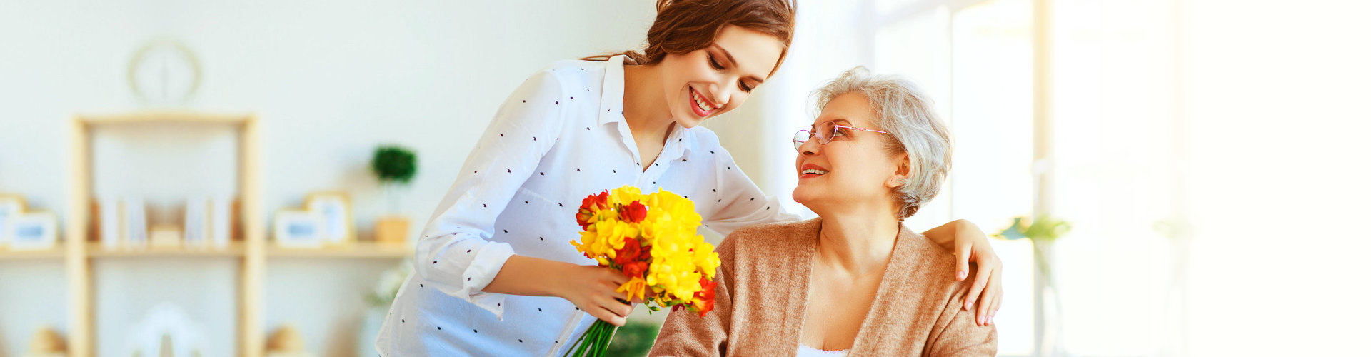 caregiver giving flowers to her senior patient