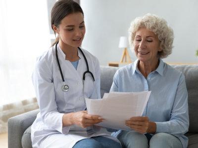nurse helping elder woman in filling up documents