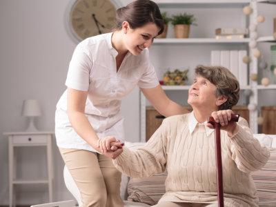 caregiver helping elder woman on stading up concept