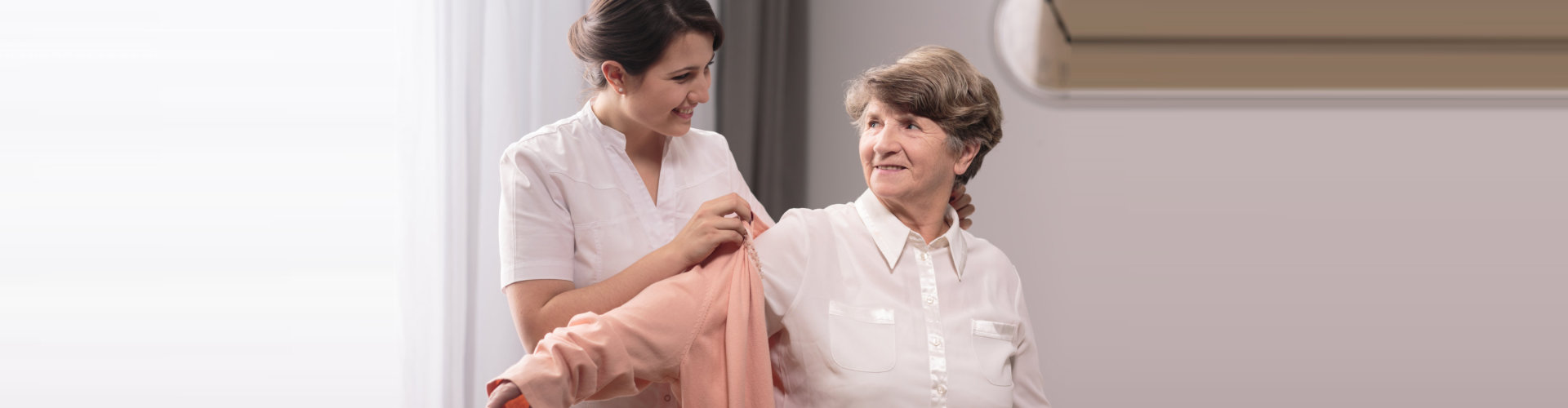caregiver assisting elder woman on wearing a cloth